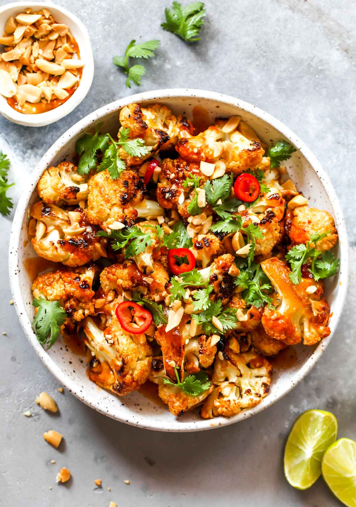 Roasted cauliflower topped with peanuts and cilantro in a white bowl