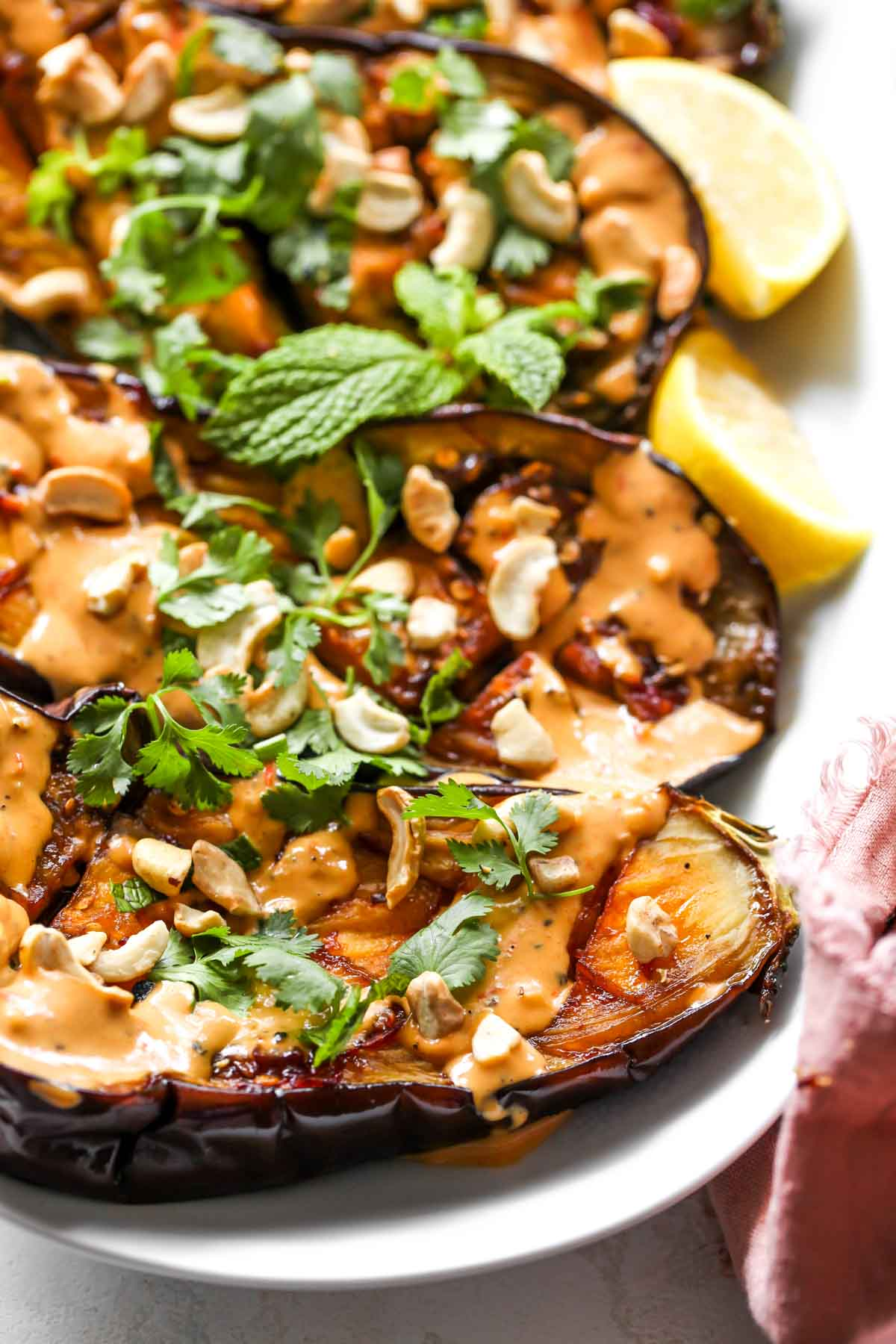 Roasted eggplant on a white platter topped with harissa-tahini sauce