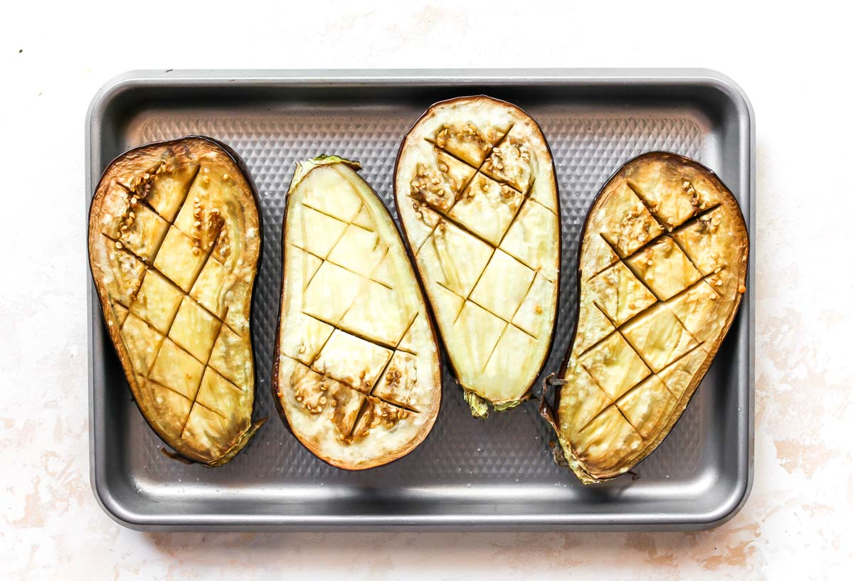 Sliced eggplant halves on a silver sheet pan