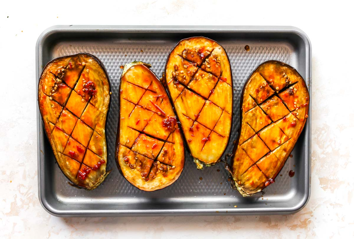 Roasted aubergine brushed with glaze on a sheet pan