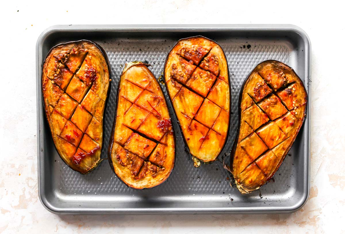 Roasted aubergine halves topped with glaze