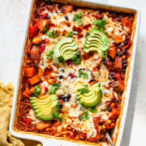 Quinoa Enchilada Casserole in a white pan topped with avocado slices