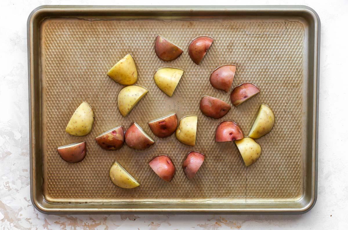 Chopped potatoes on a gold baking sheet