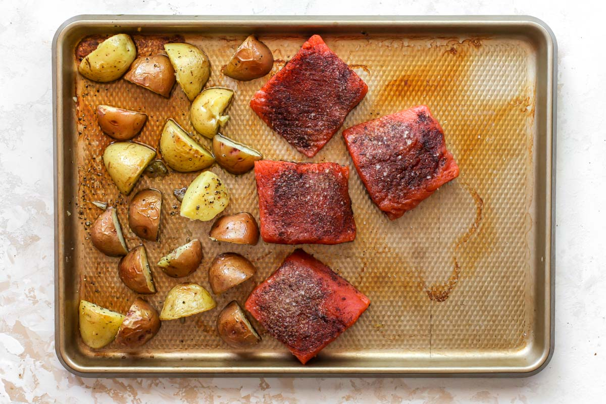 Potatoes and salmon fillets on a gold sheet pan