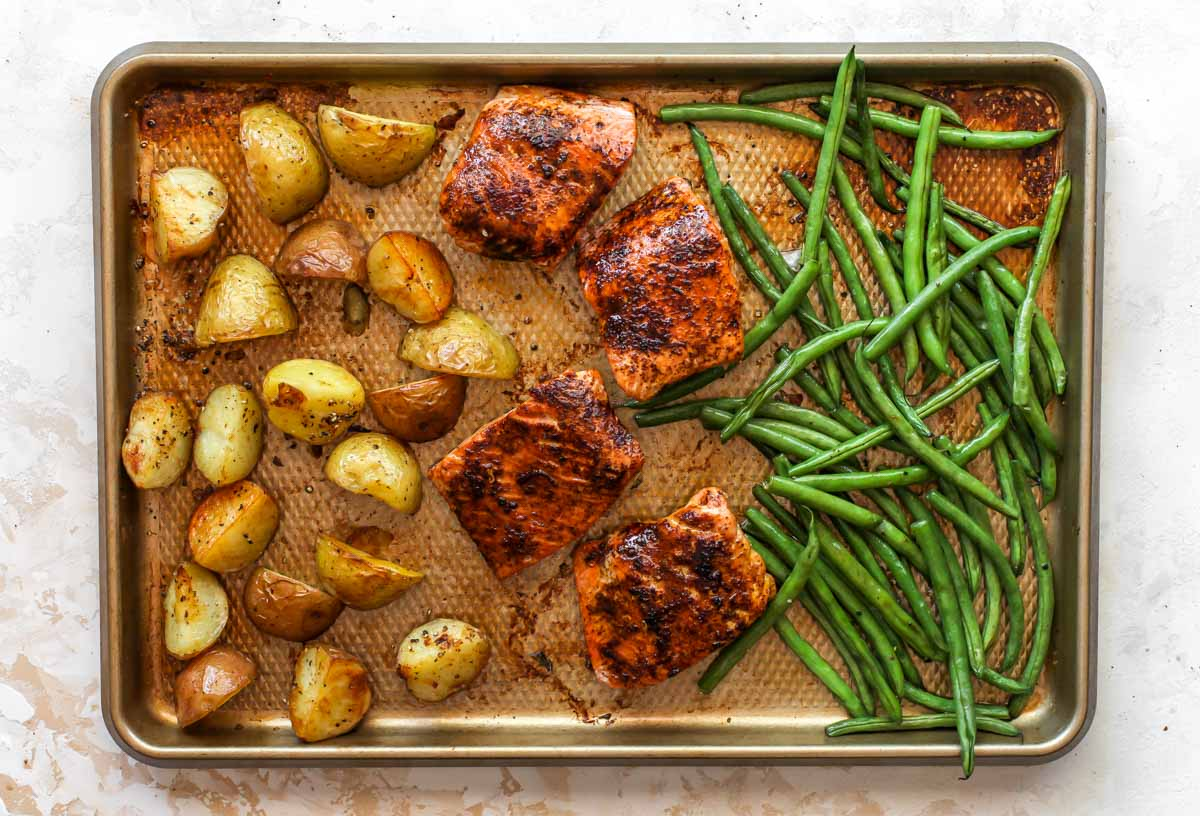 Potatoes, salmon fillets, and green beans on a gold baking sheet