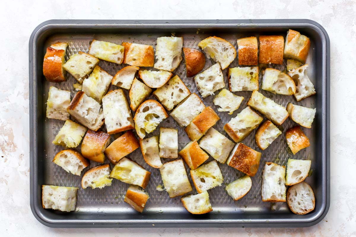 Cubed bread on a sheet pan tossed in olive oil