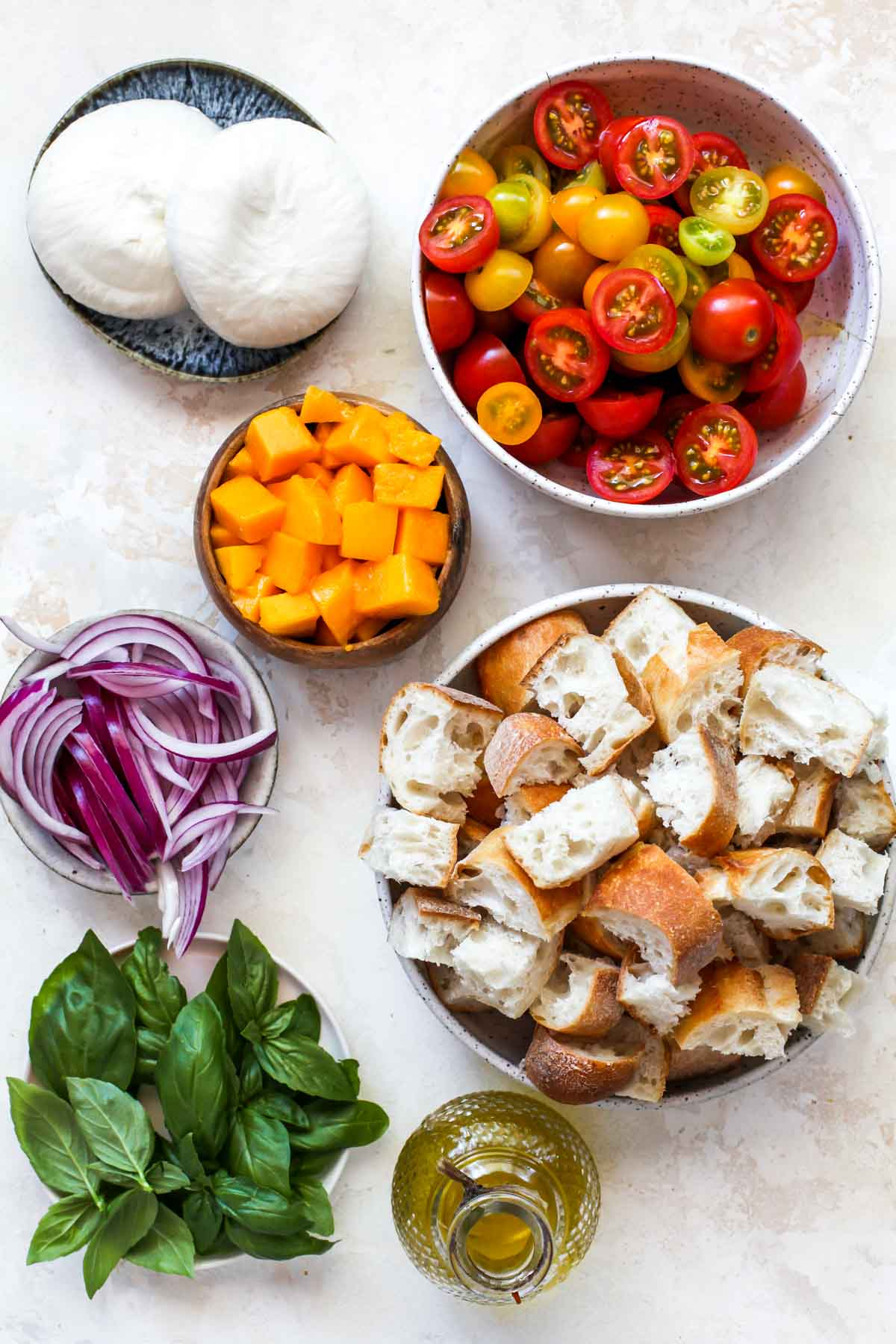 Tomatoes, bread, basil, mango, and red onion in separate bowls