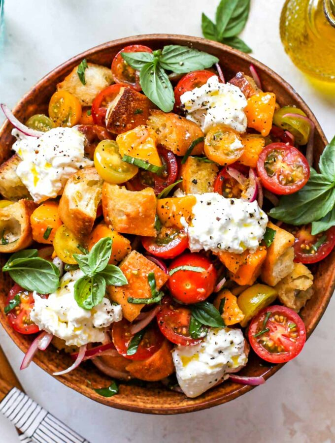 Tomato and bread salad with cheese and basil in a gold bowl
