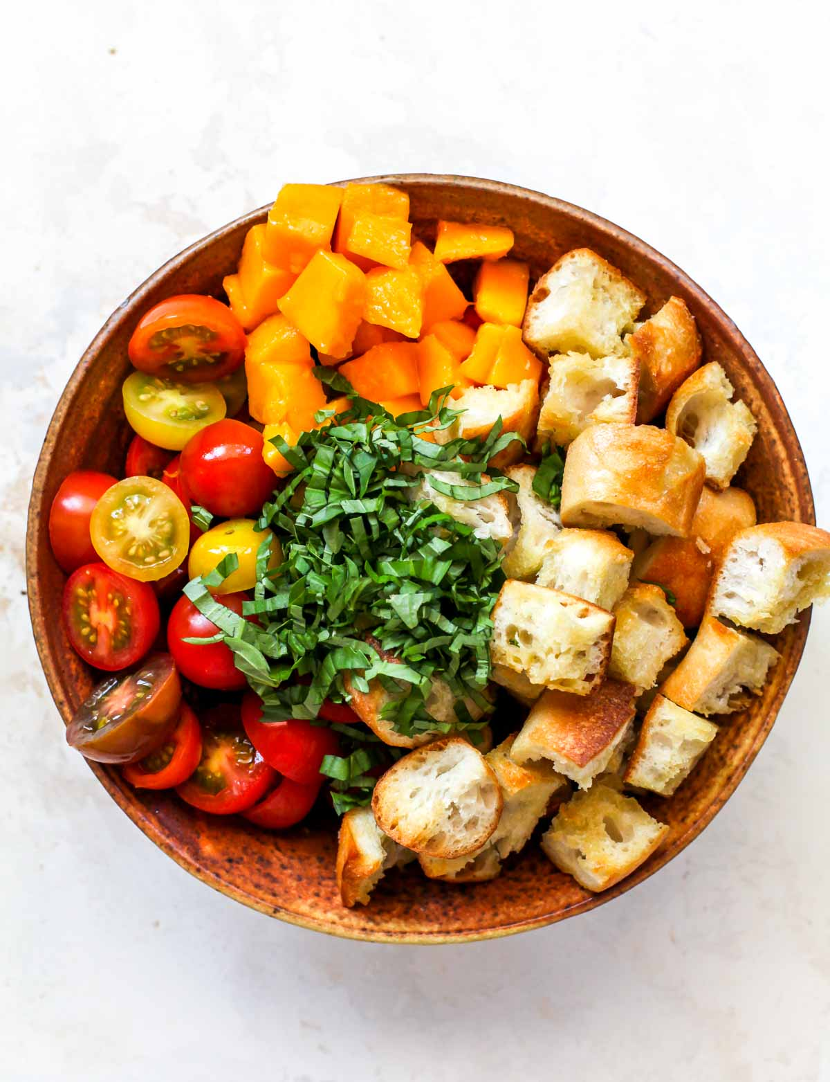 Tomatoes, cubed bread, basil, and mango in a large orange bowl