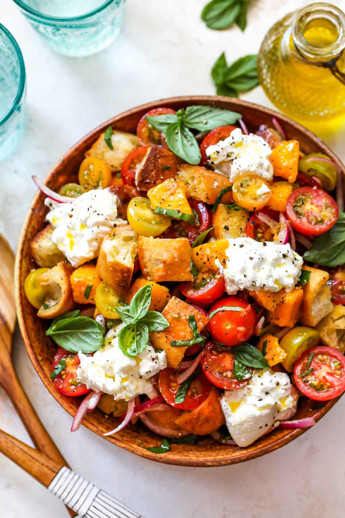 Tomatoes, bread, basil, and cheese in an orange bowl