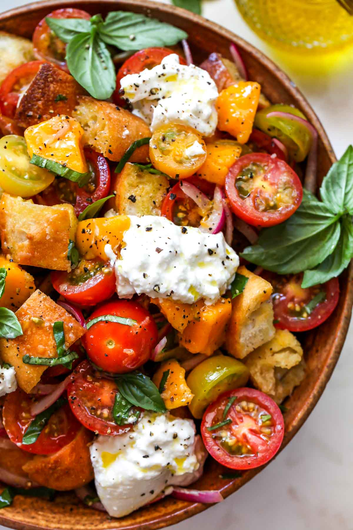 Close up on panzanella salad topped with burrata cheese