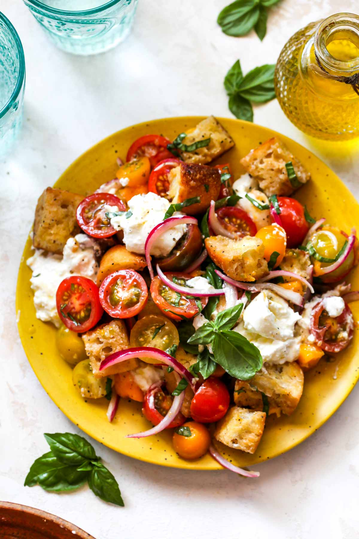 Panzanella salad served on a yellow plate topped with basil