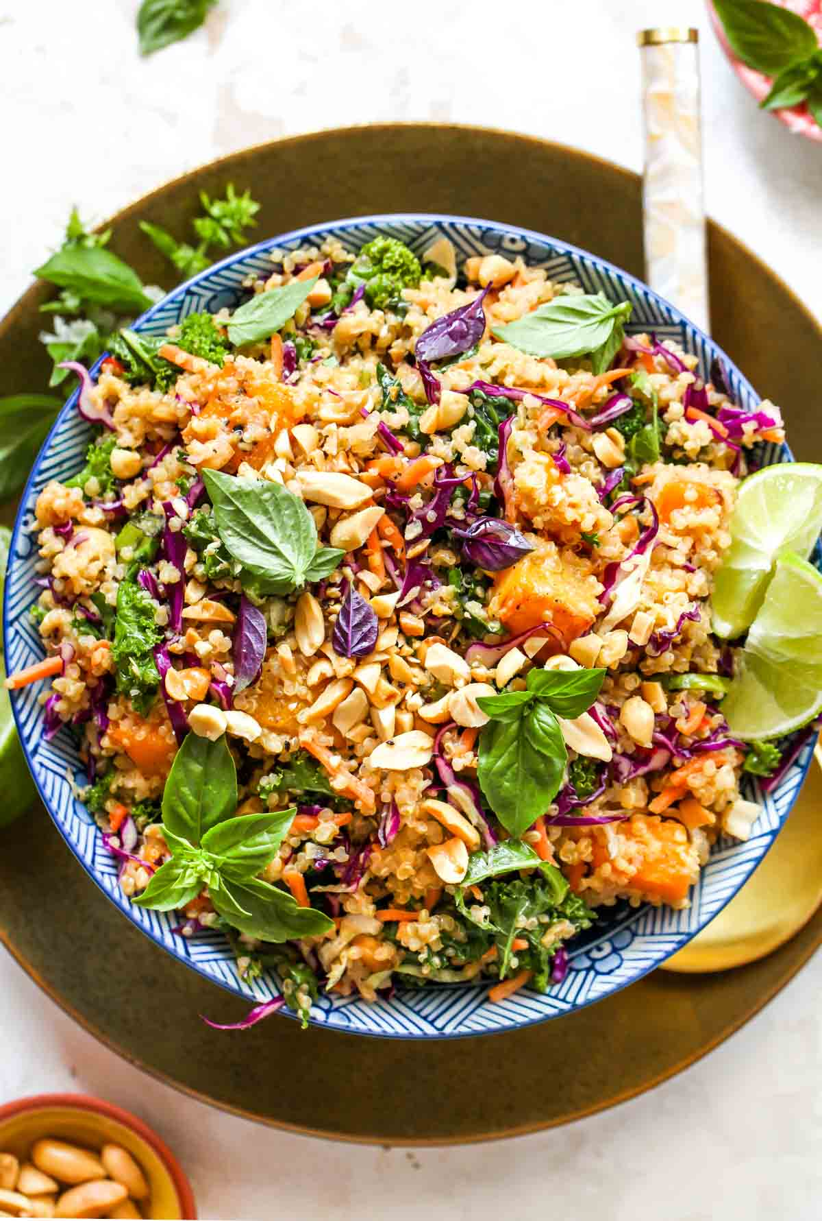 Quinoa and butternut squash salad in a blue bowl on a gold plate