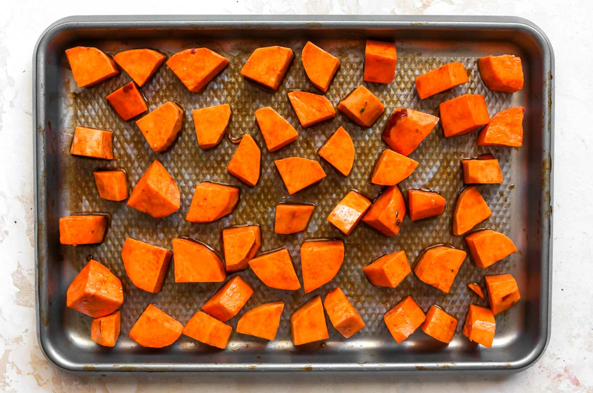 Cubes of sweet potatoes tossed in oil and spices on a baking sheet