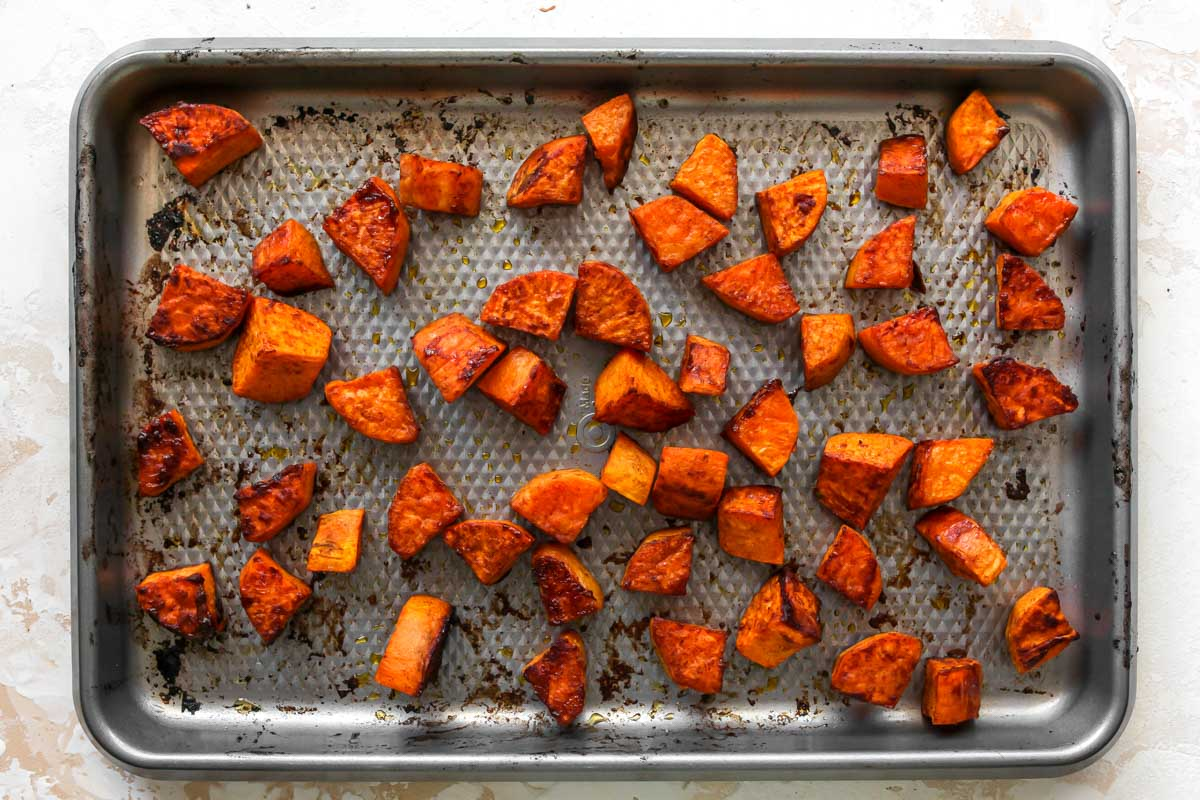Roasted sweet potatoes on a silver sheet pan