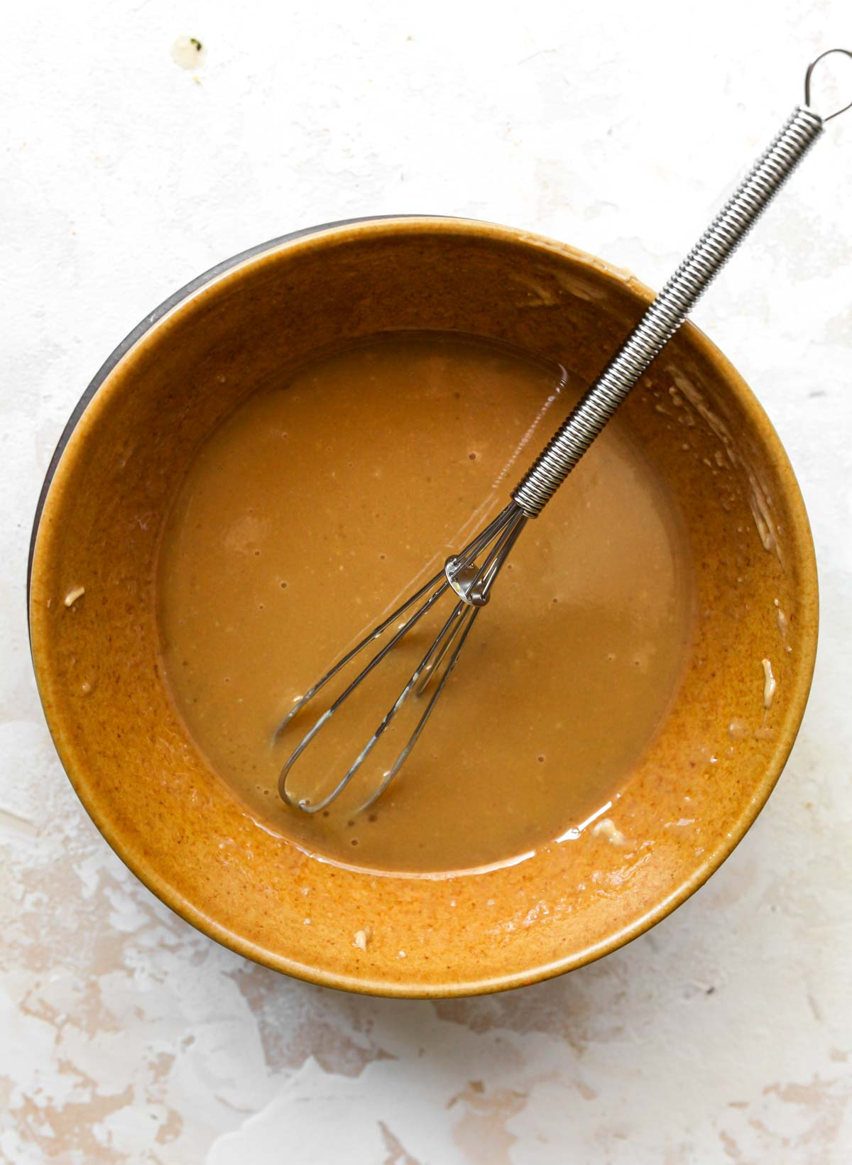 Maple vinaigrette being whisked in a gold bowl