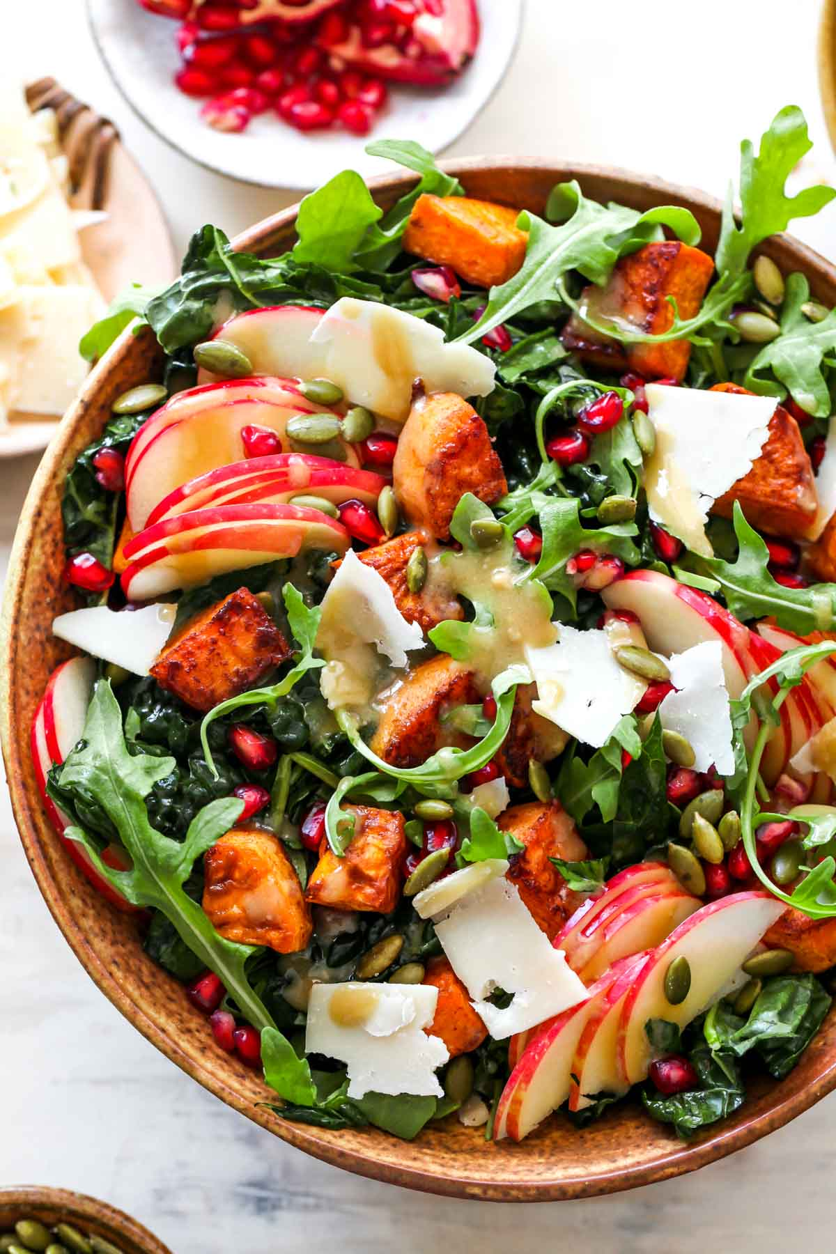 Fall salad in a gold bowl with greens, roasted sweet potatoes, and maple dressing