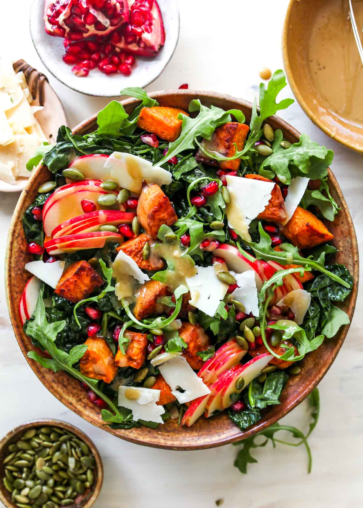 Kale salad topped with sweet potatoes, apples, and pomegranate seeds