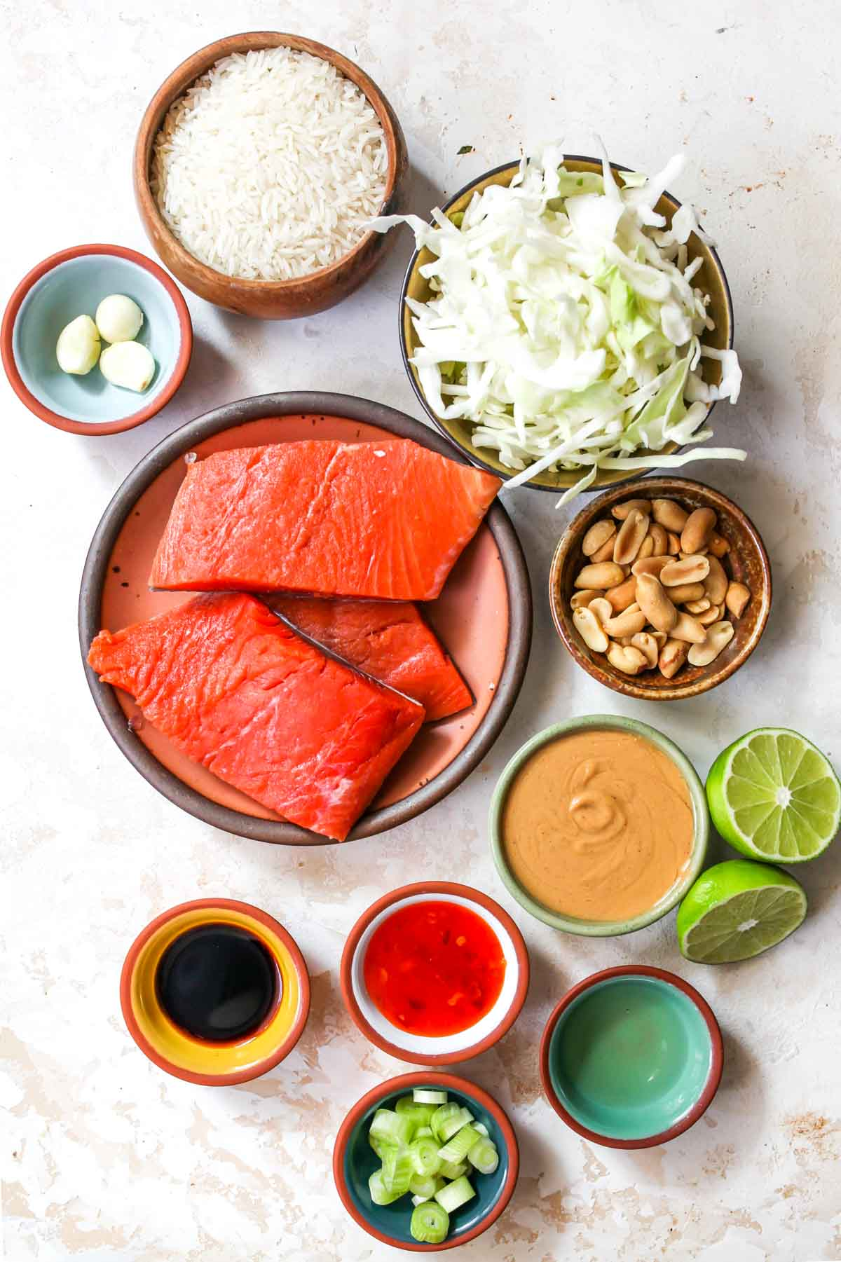 Recipe ingredients including salmon, rice, slaw, and peanut sauce ingredients on a white board