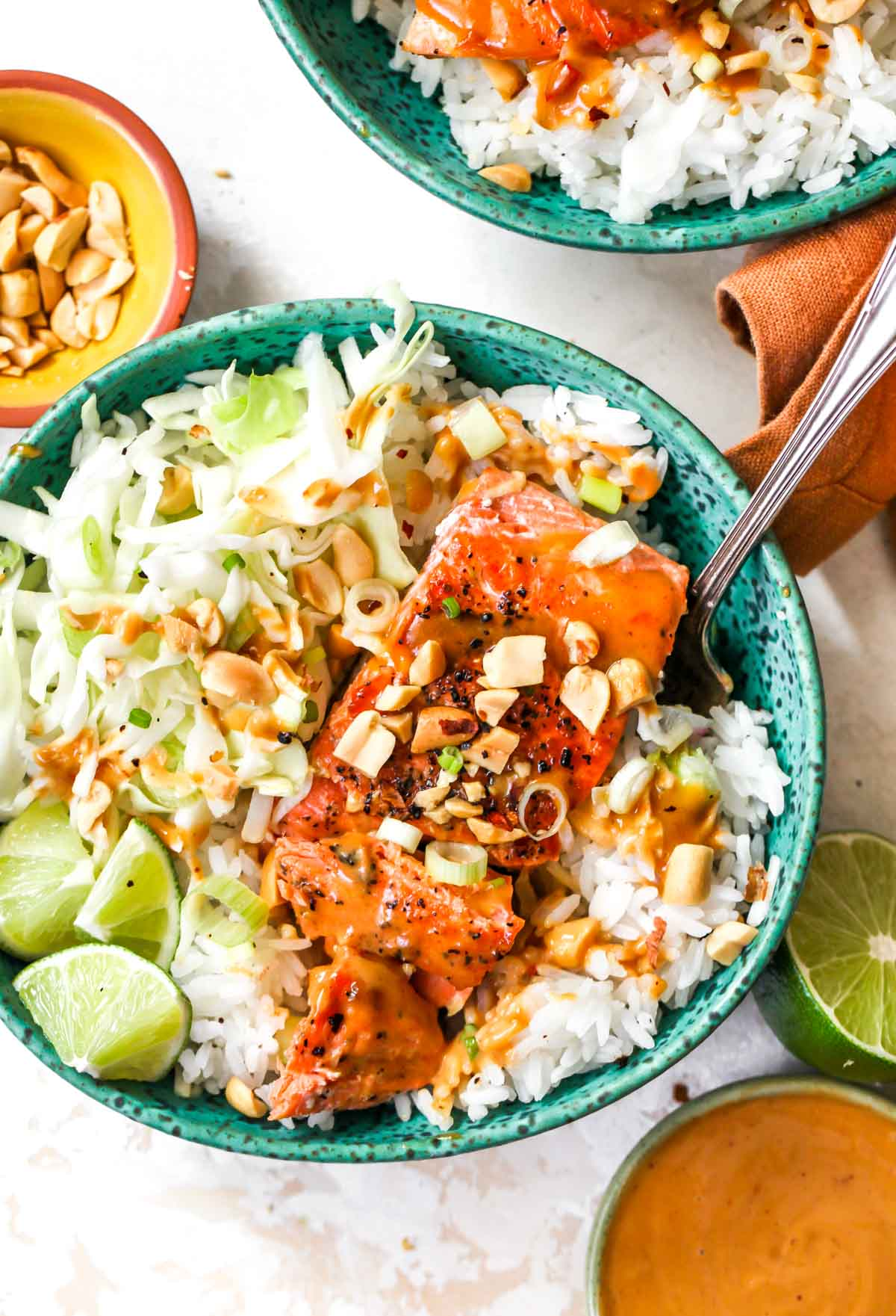Seared salmon over rice with slaw and peanut sauce in a blue bowl