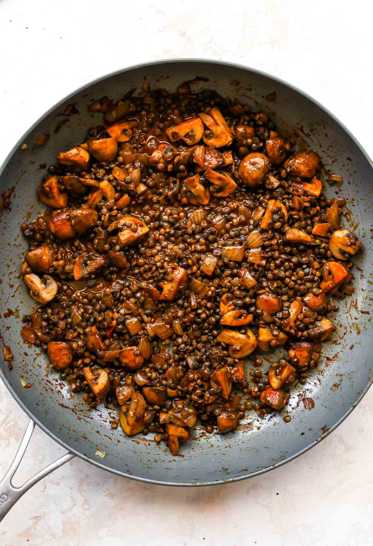 Mushrooms and lentils simmering in a skillet