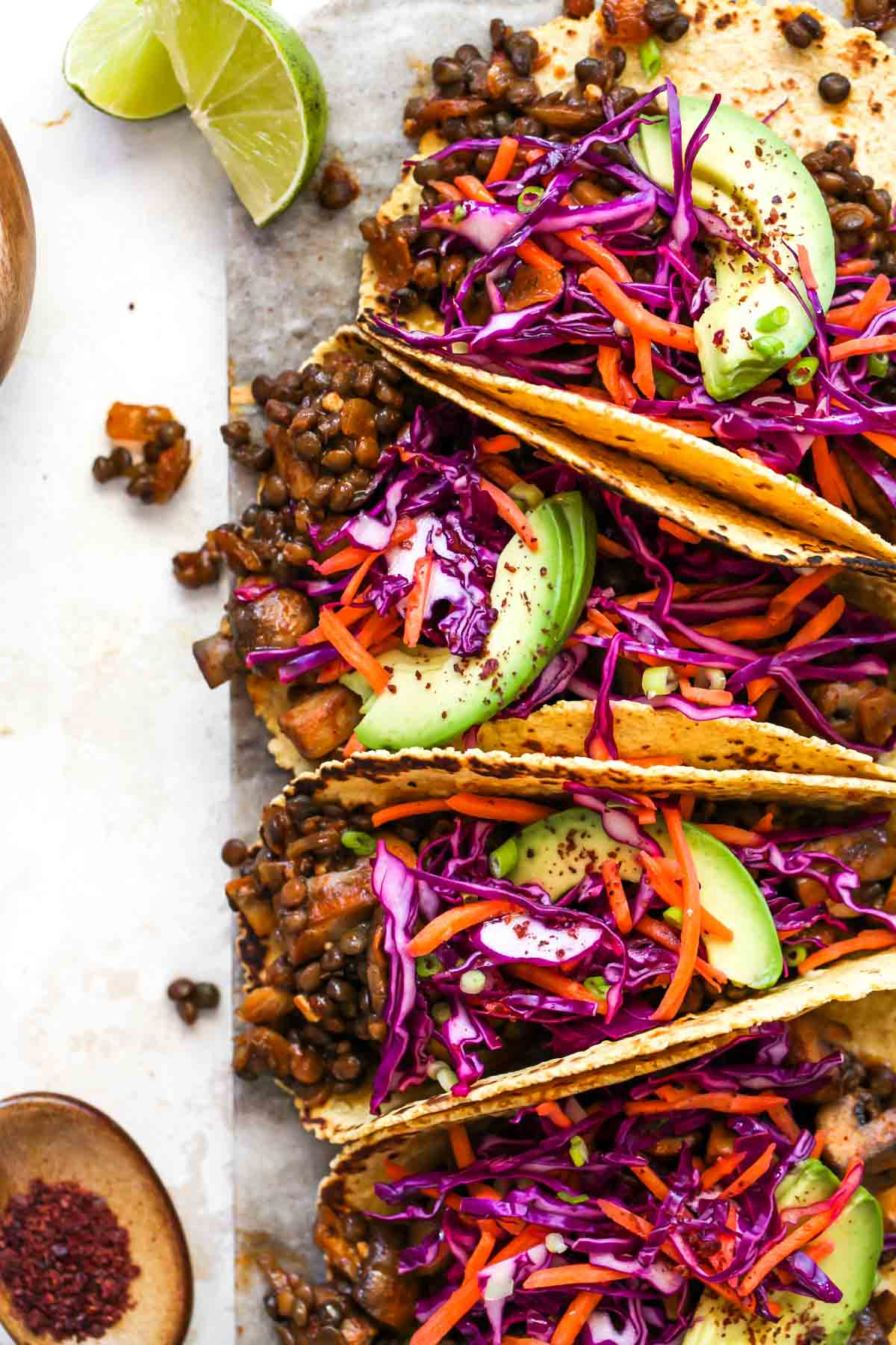 Mushroom and lentil tacos topped with cabbage slaw and avocado