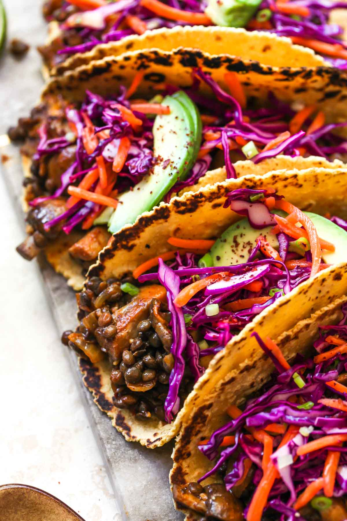 Vegetarian taco filling topped with cabbage slaw and sliced avocado