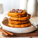 Stack of pumpkin protein pancakes being drizzled with syrup