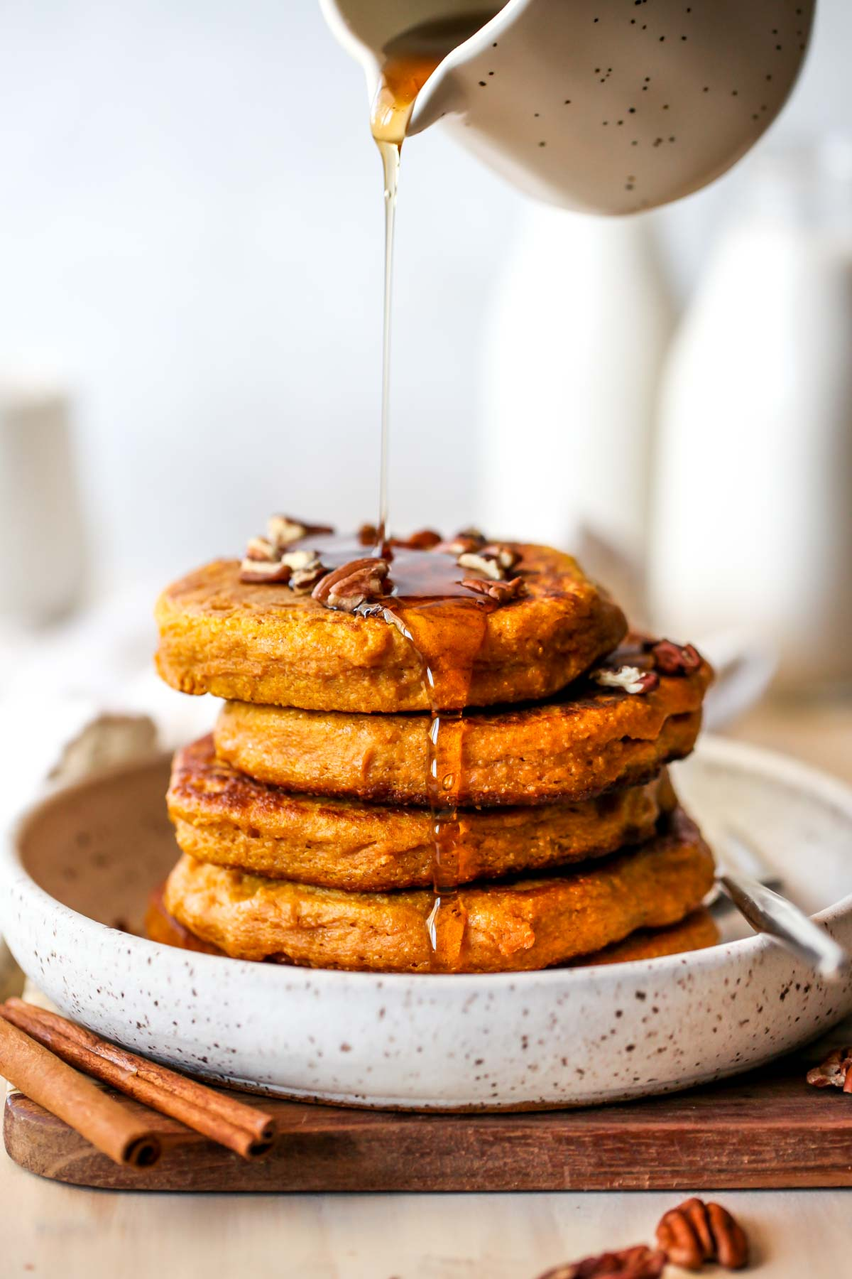 Stack of pancakes being drizzled with maple syrup