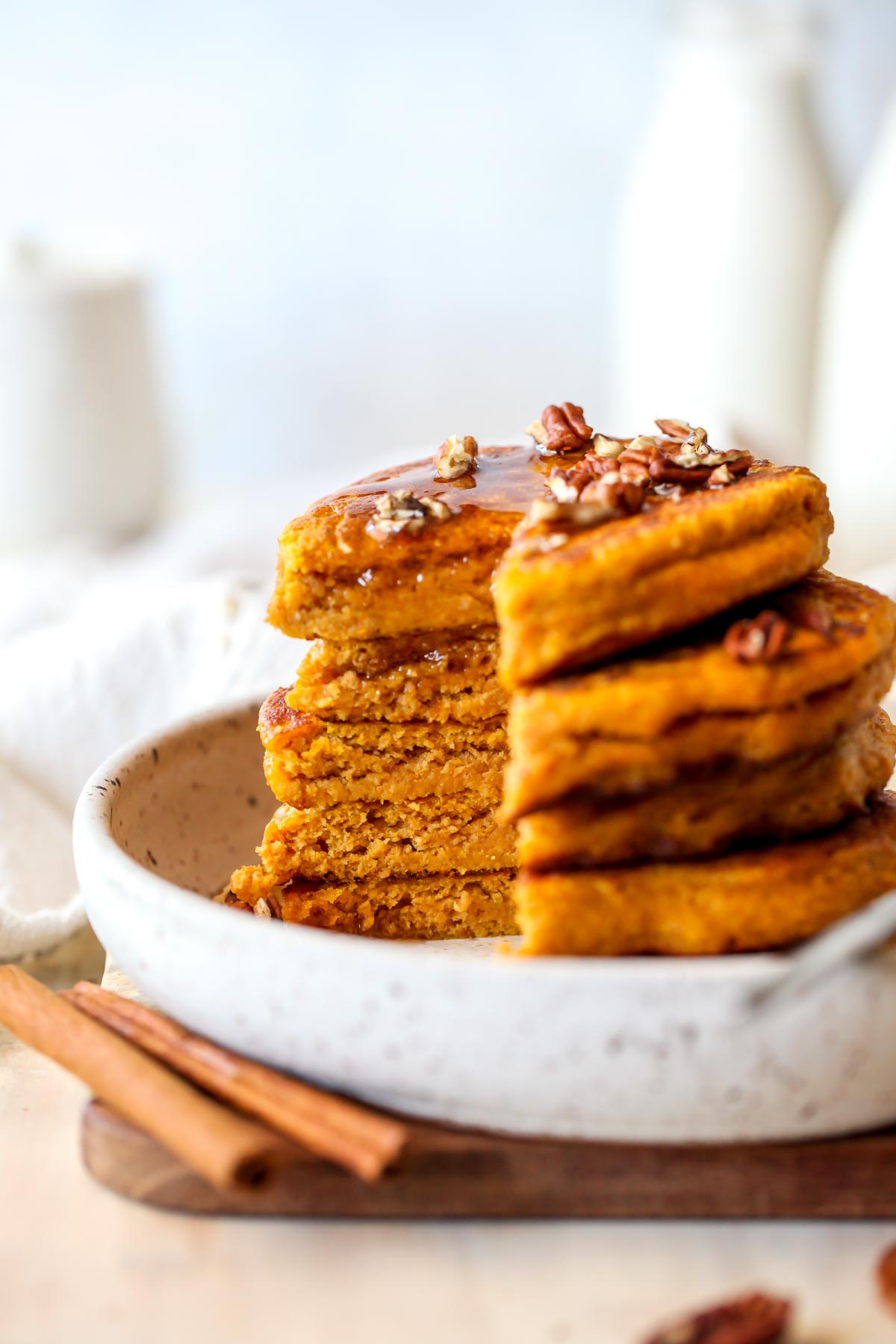 Stack of pumpkin pancakes being sliced into to reveal fluffy insides