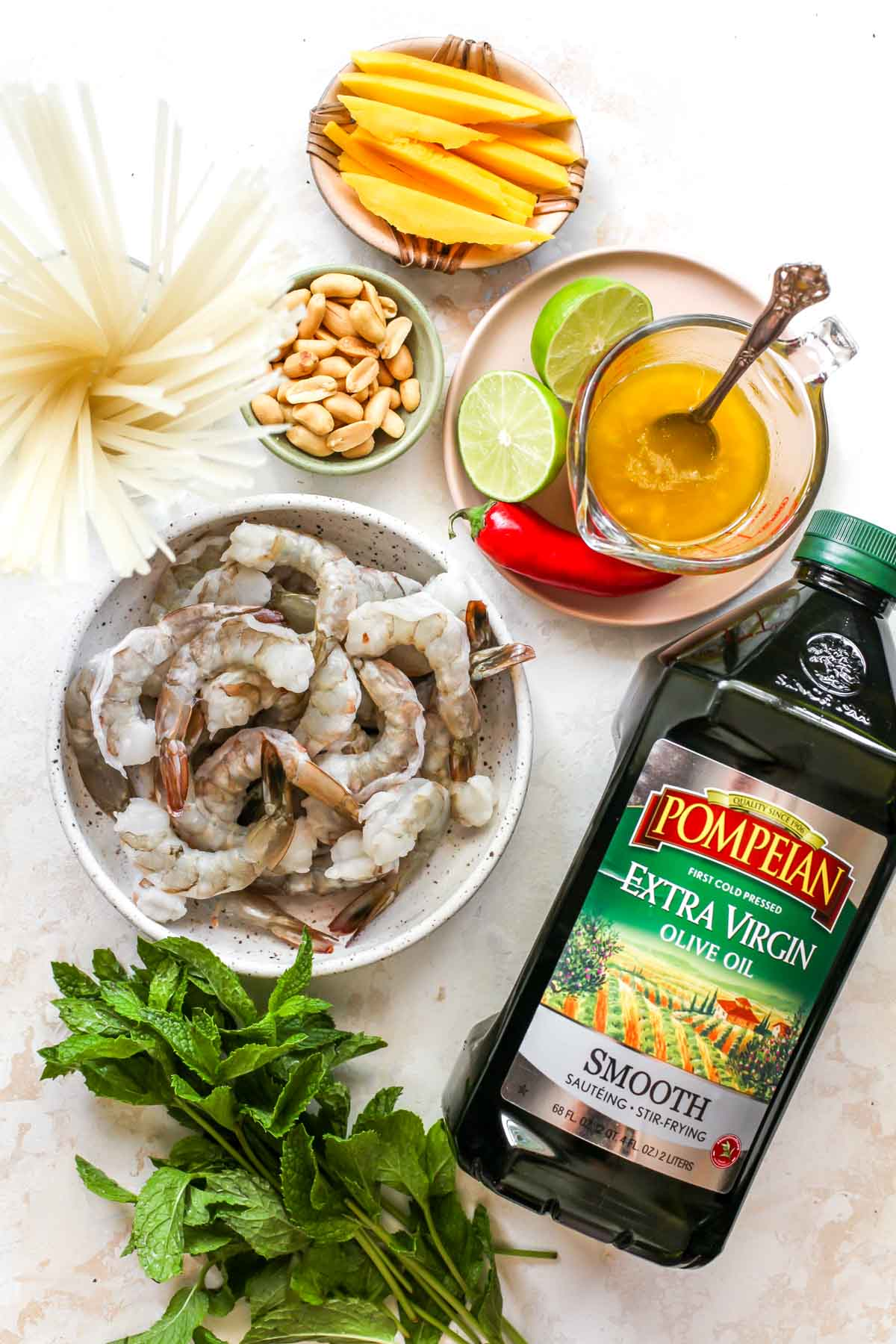 Ingredient overlay with olive oil, raw shrimp, and ginger dressing