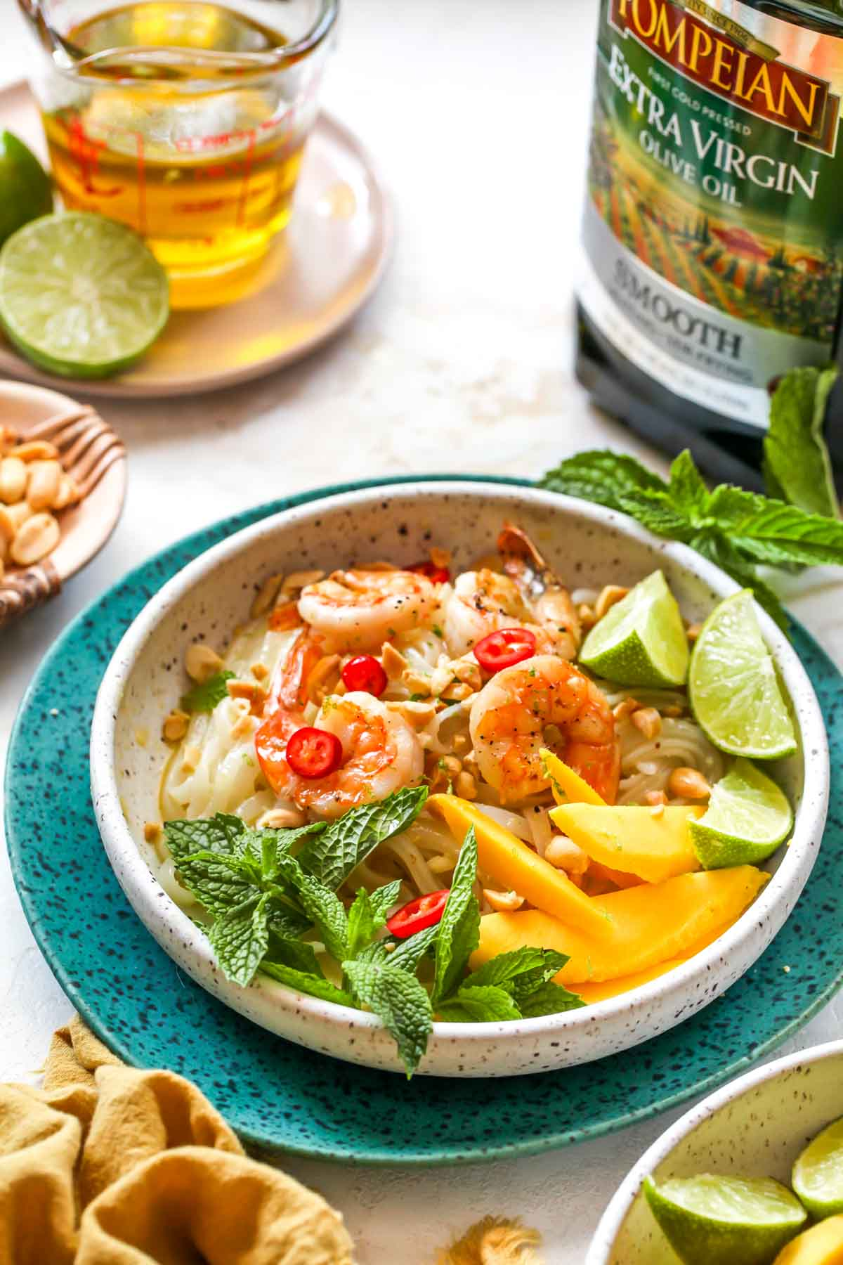 Seared shrimp and noodles in a white bowl garnished with mint and mango