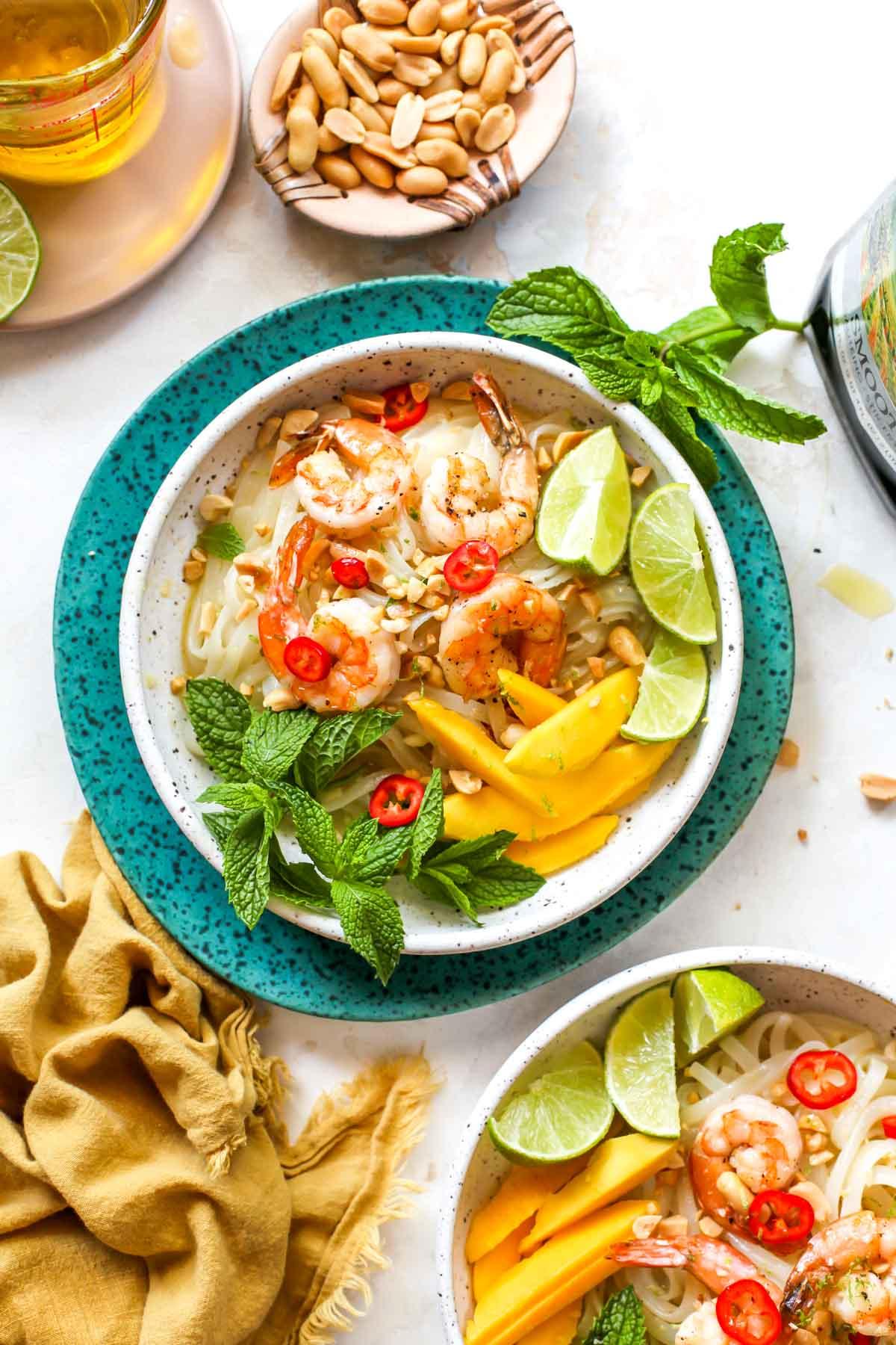 Shrimp noodle salad tossed with ginger dressing in a tan bowl