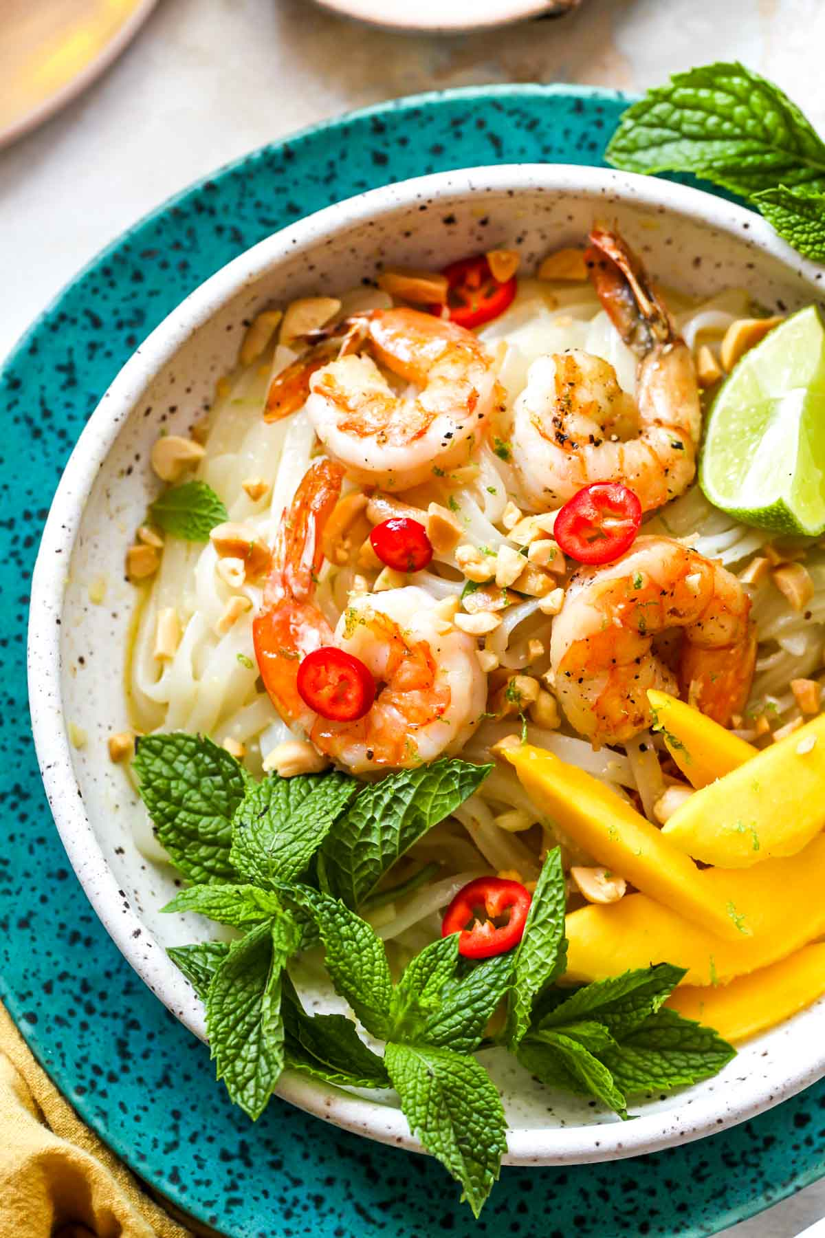 Shrimp and glass noodles in a bowl topped with mint and mango