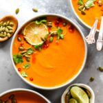 Thai pumpkin soup in a grey bowl topped with chili oil and herbs