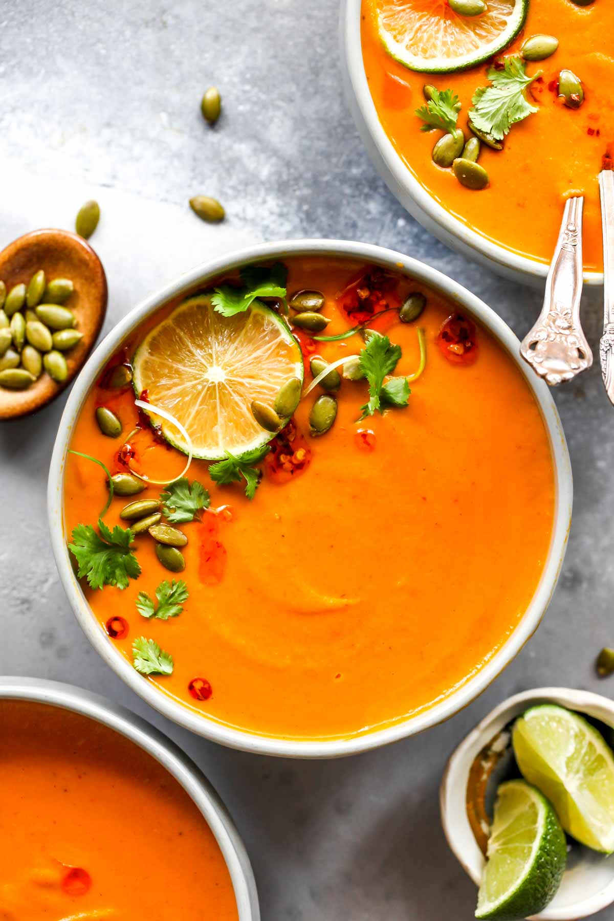 Creamy Thai Pumpkin Soup in a grey bowl topped with cilantro and lime