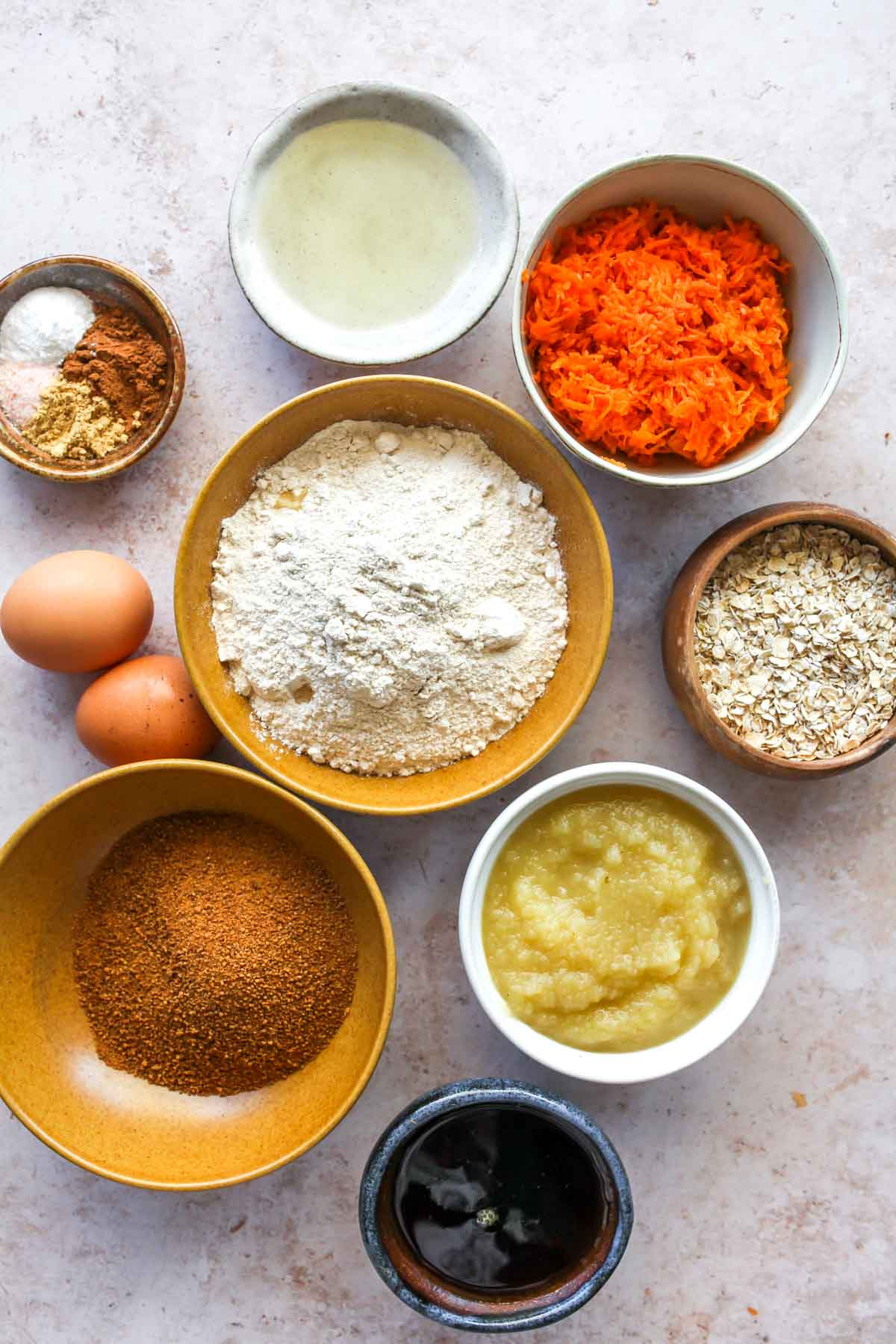 Carrot apple bread ingredients in separate bowls on a white board