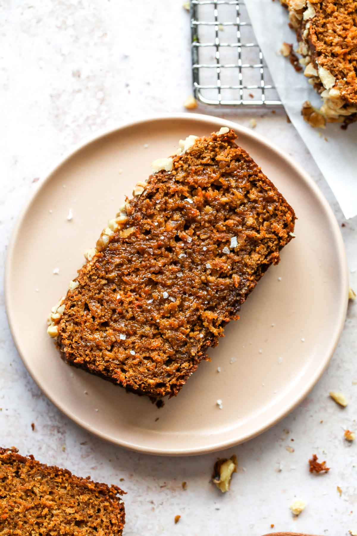 Slice of carrot apple bread on a pink plate topping with butter