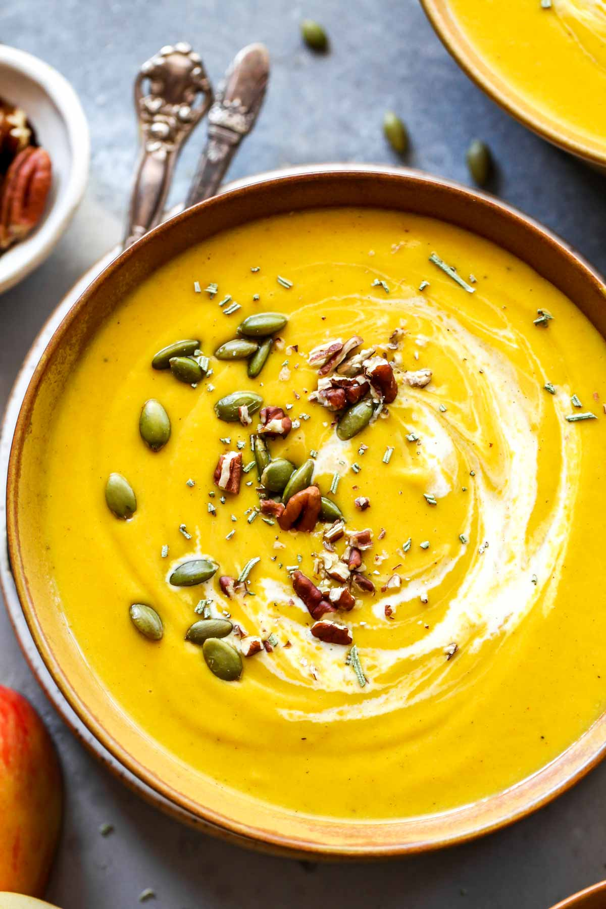 Close up of butternut squash soup in a bowl with a spoon resting on the side