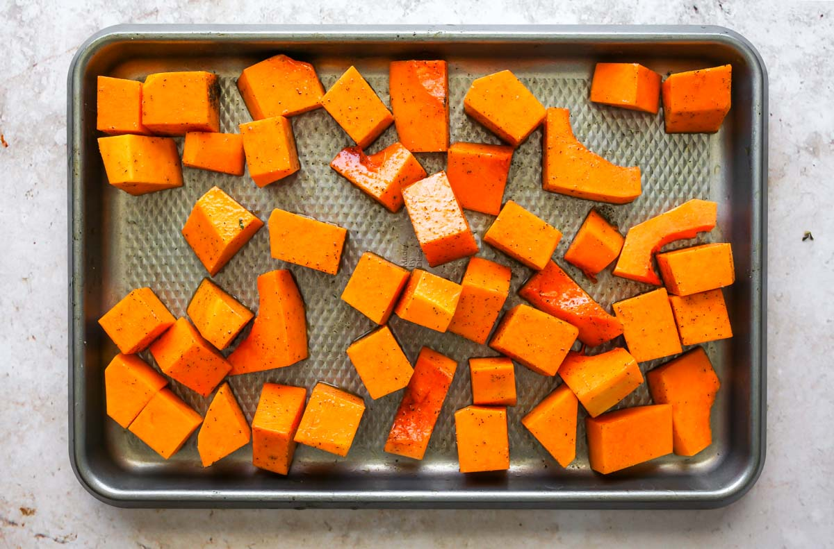 Butternut squash cubes on a silver baking sheet