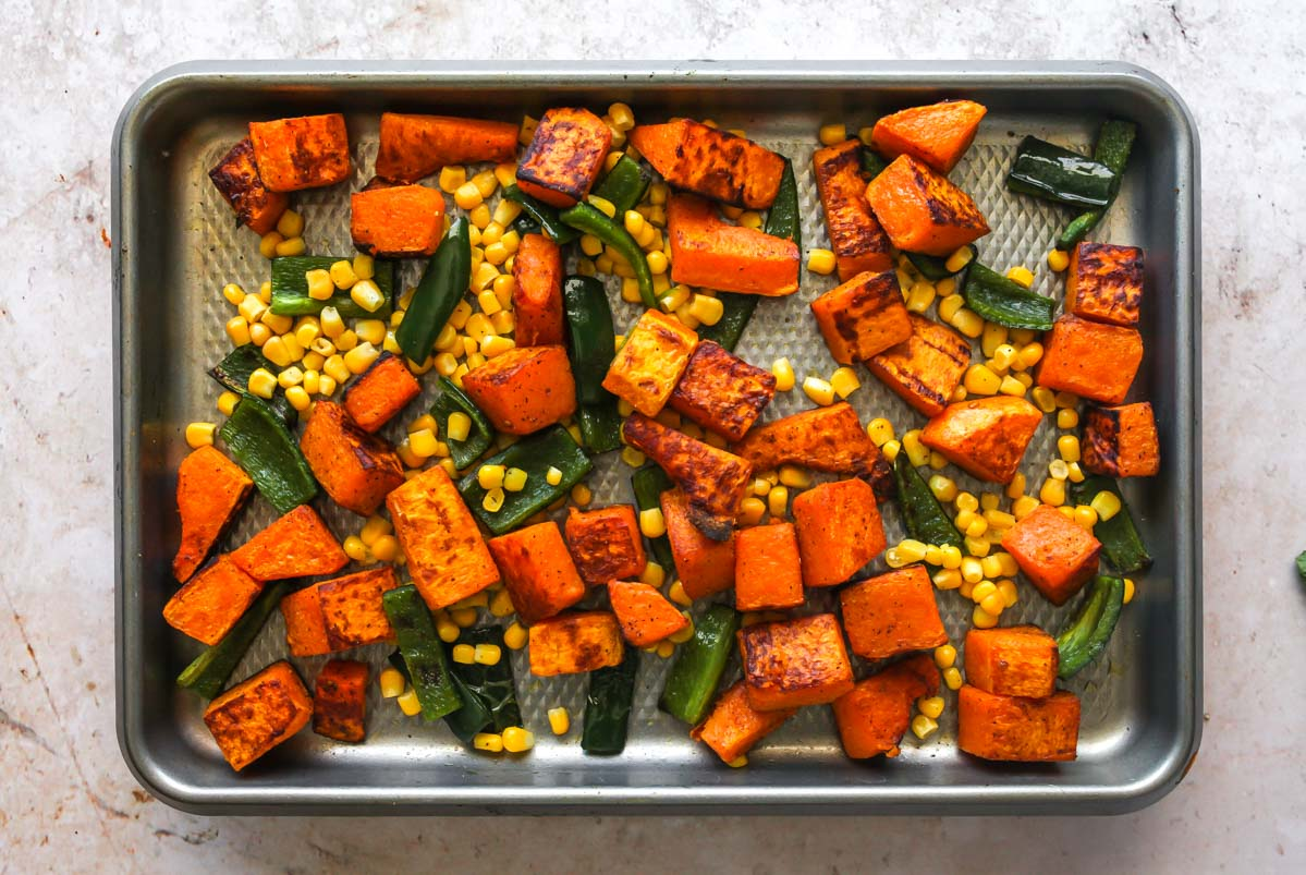 Corn, squash, and peppers being mixed together on a baking sheet
