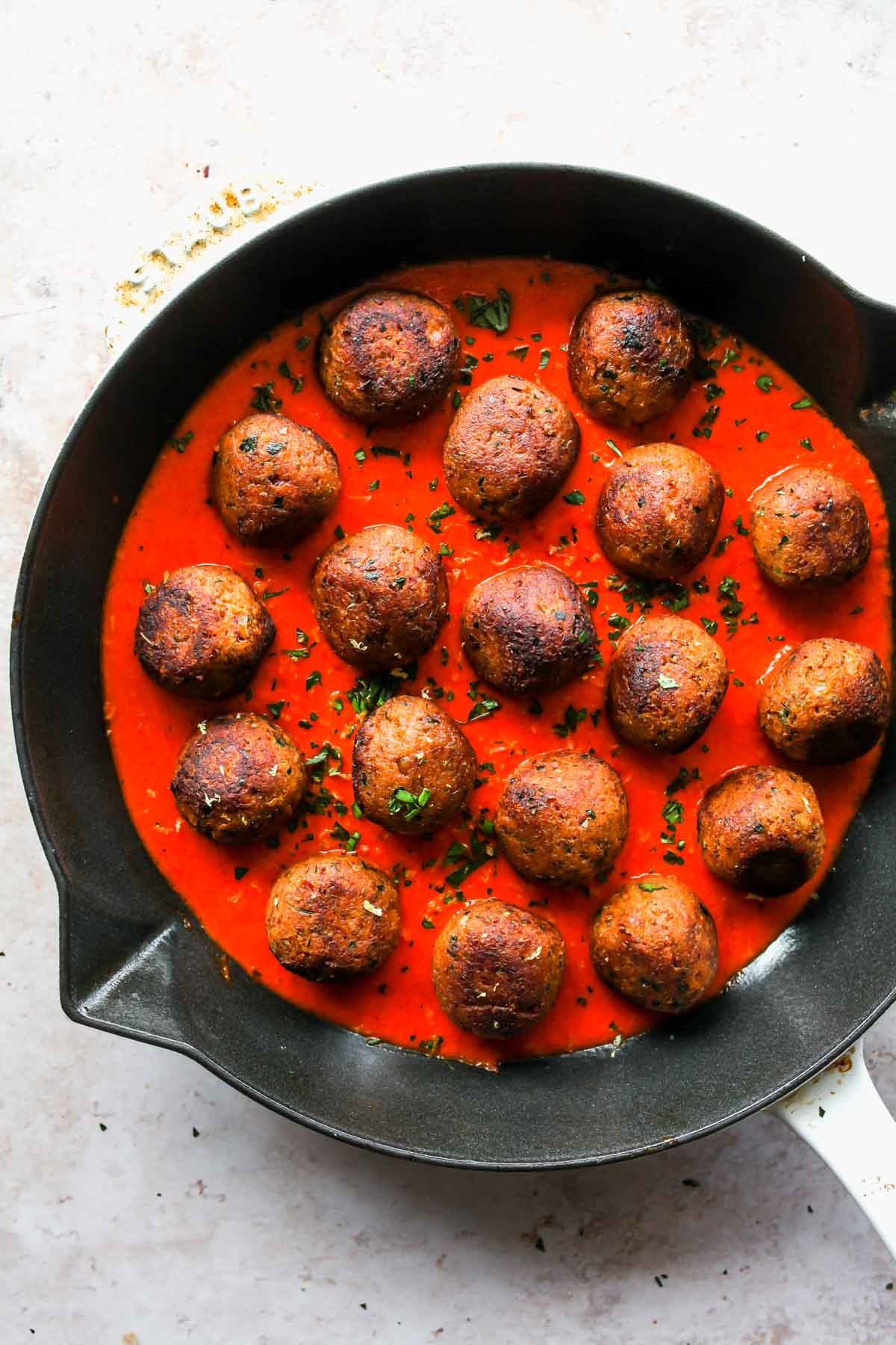 Lentil meatballs in a skillet topped with roasted red pepper sauce