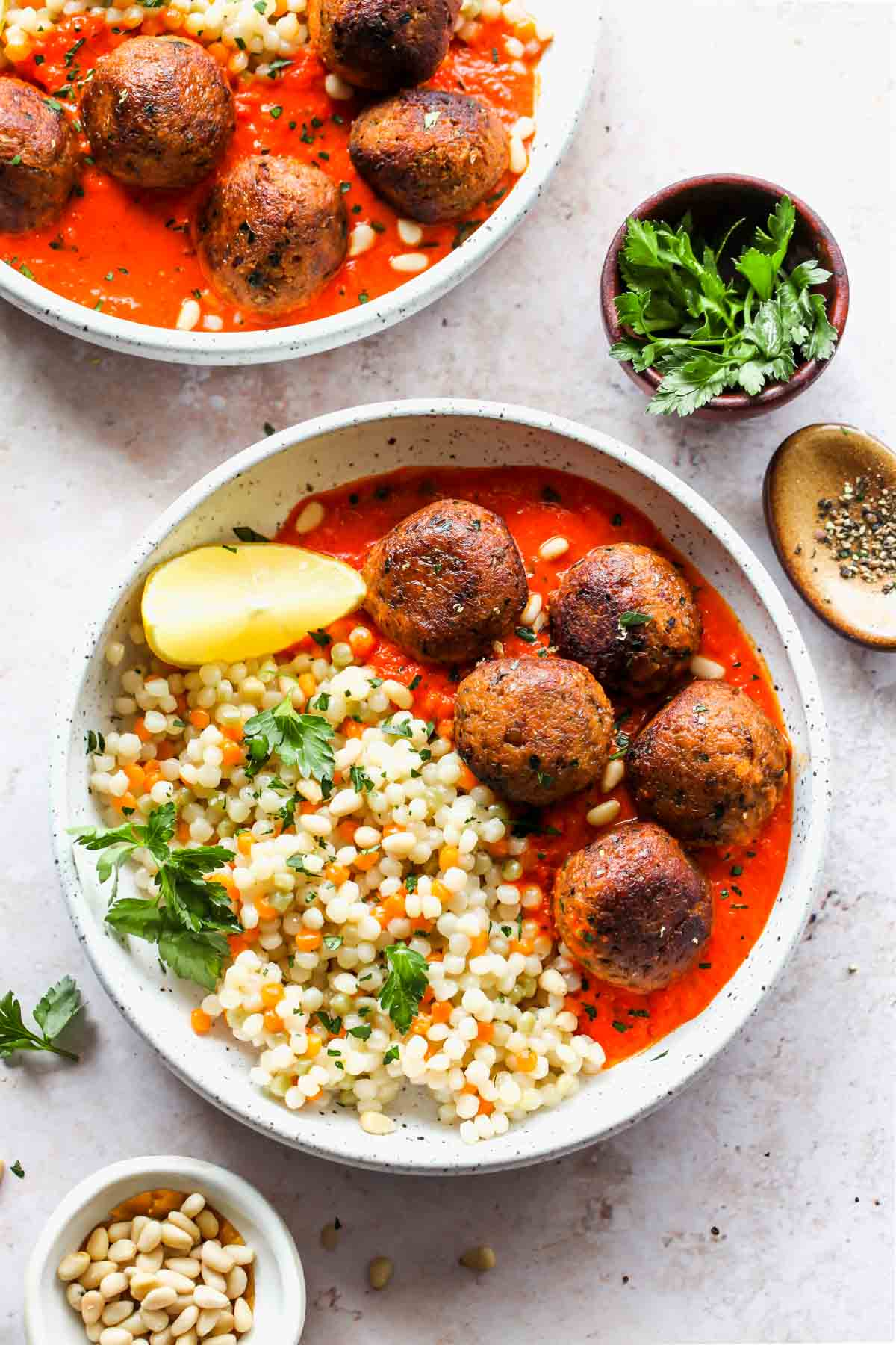 Moroccan meatballs and pearl couscous in a white bowl with lemon garnish