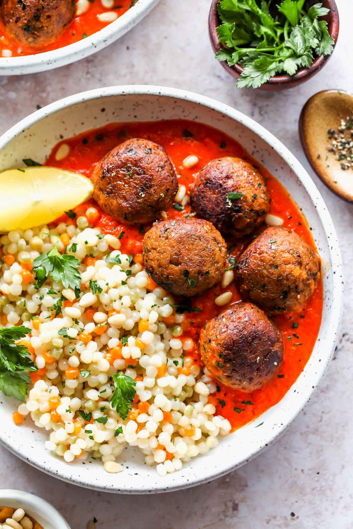 Lentil meatballs in roasted red pepper sauce with pearl couscous