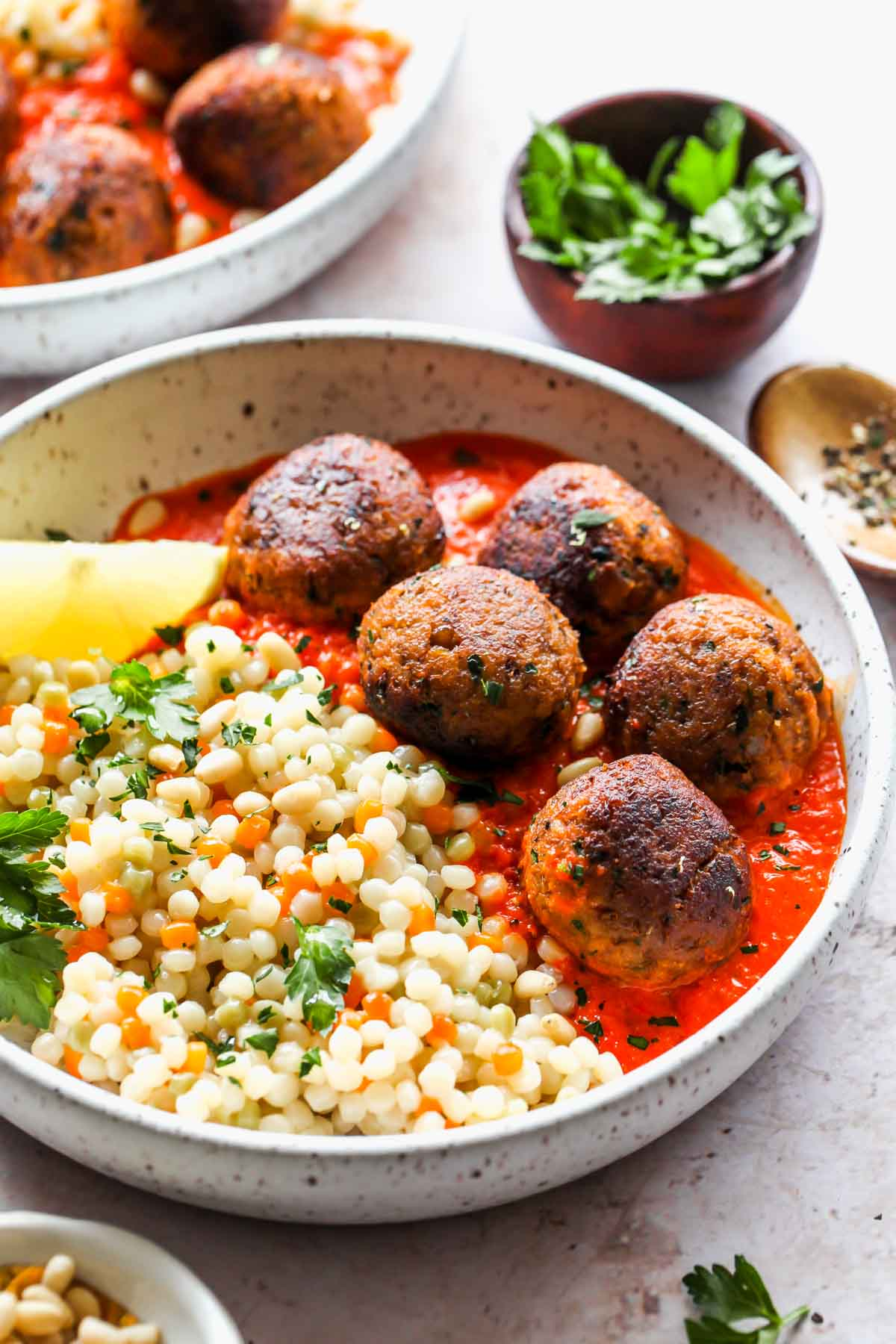 Couscous and veggie meatballs on a white plate topped with parsley