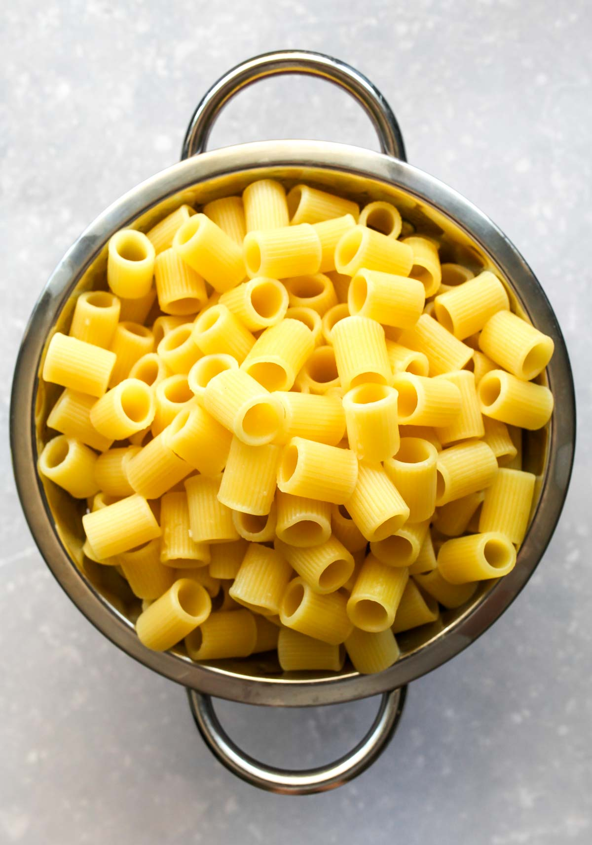 Cooked and drained pasta in a red strainer