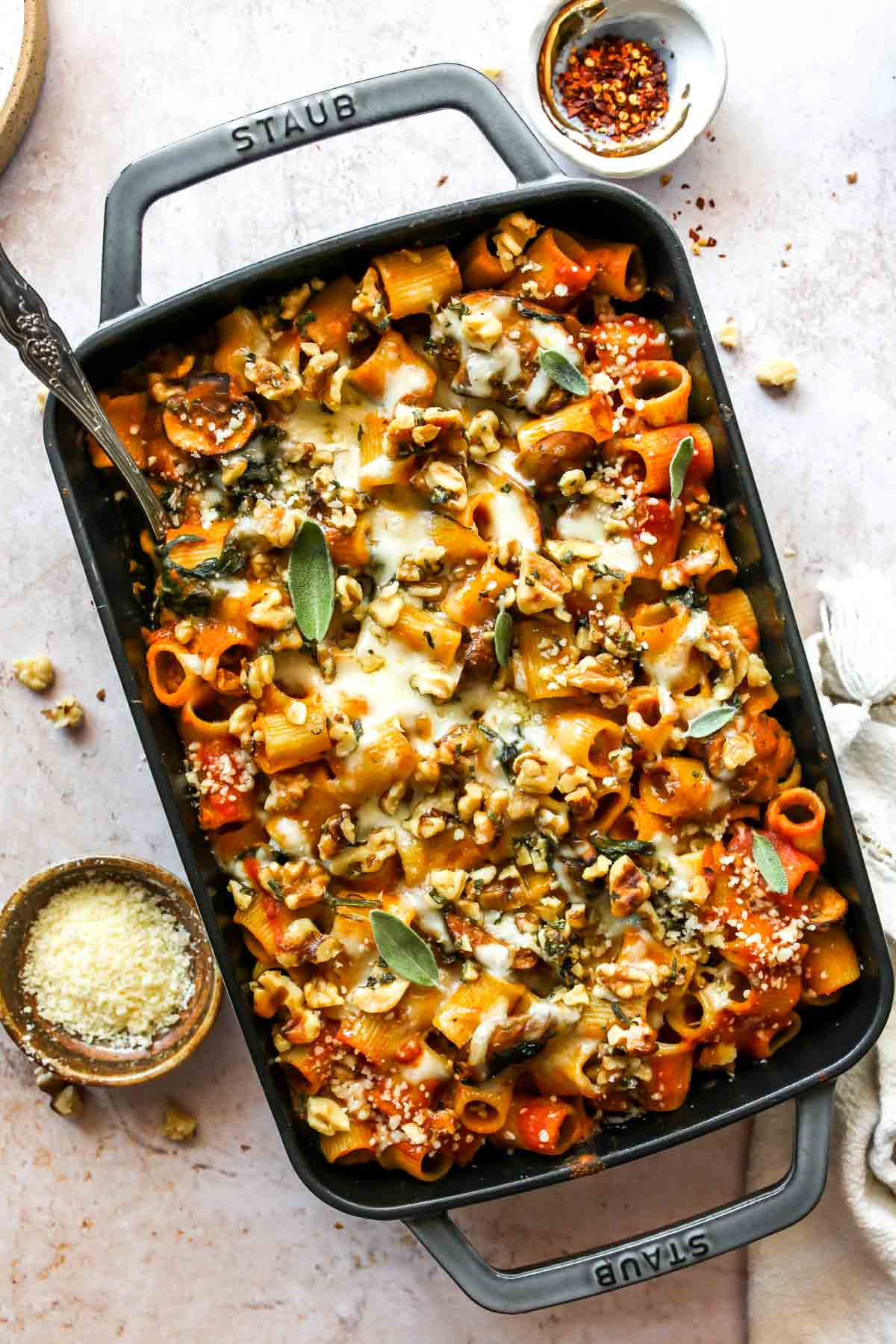 Cheesy pumpkin pasta in a baking dish topped with walnuts and sage