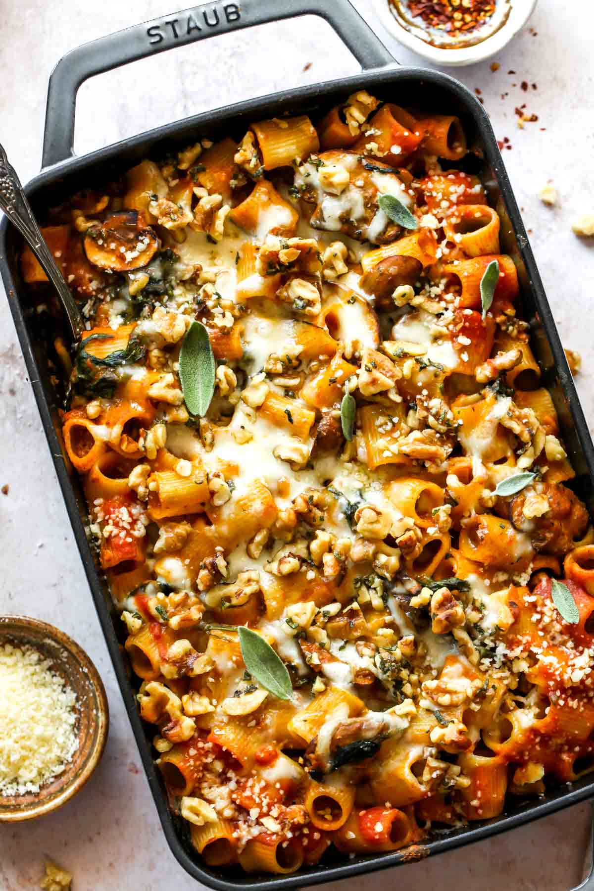 Rigatoni in a baking pan with tomato sauce topped with cheese