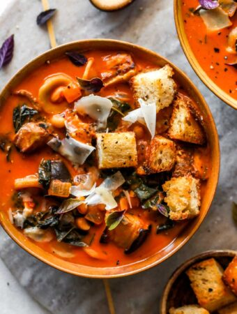 Roasted eggplant and tomato soup in a gold bowl topped with croutons