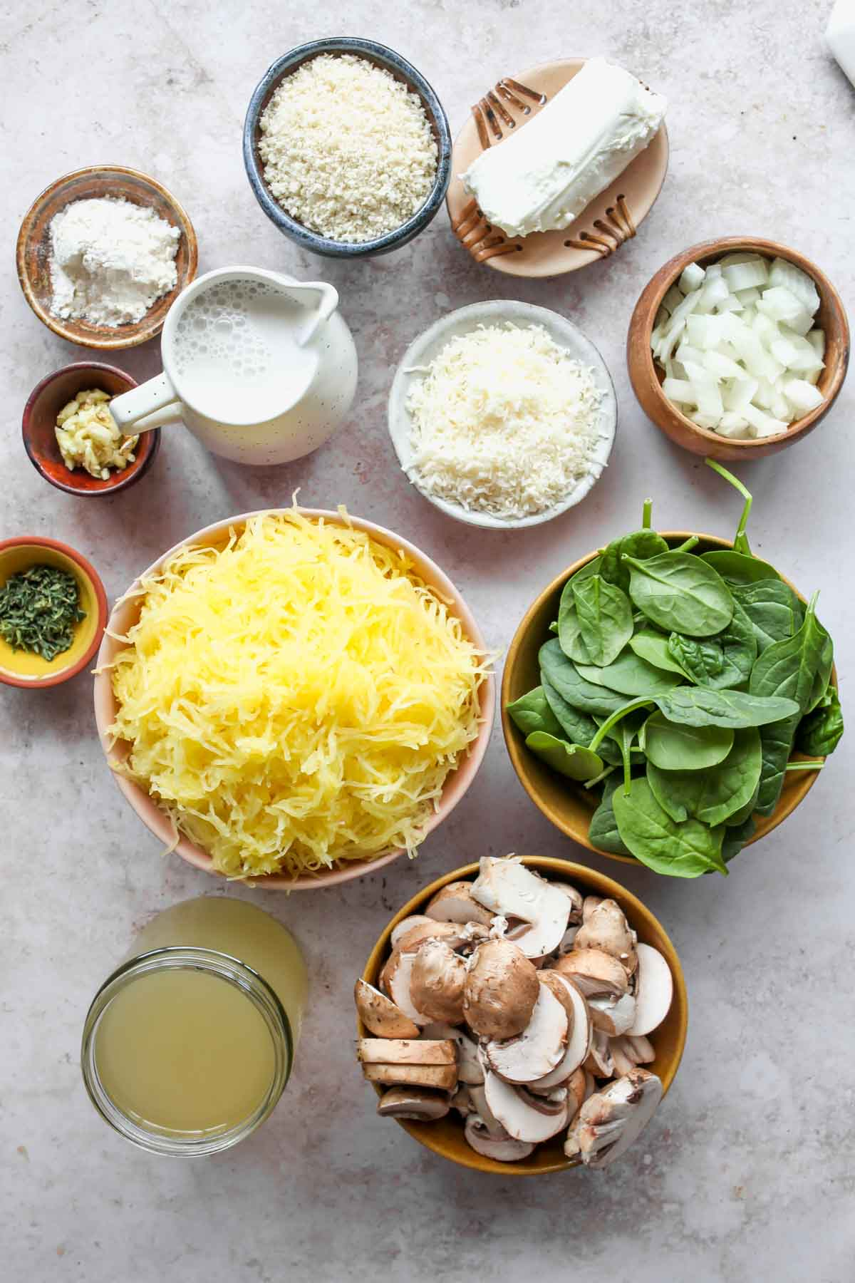 Spaghetti squash casserole ingredients in separate bowls on a white board